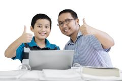Preteen student and his teacher show thumbs up. Picture of preteen student showing thumbs up with his teacher while using a laptop in the studio Stock Photo