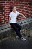 Preteen waiting. A young preteen boy waiting by a red brick wall at a school, looking bored. Shallow depth of field Stock Photo