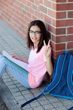Preteenager girl with the backpack sitting on the floor Royalty Free Stock Photos