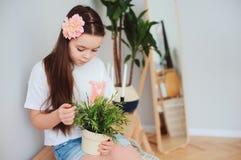 preteenflicka som hemma tar omsorg av houseplants Arkivbilder