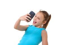 Preteenflicka som tar självporträttet med mobiltelefonen Arkivbild