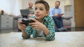 Preteenjongen het spelen videospelletje, papa en opa, vrije tijd en hobby die glimlachen stock footage