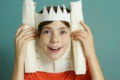 Preteenpojken med rik fantasi gör konung från tunt bröd Royaltyfri Foto