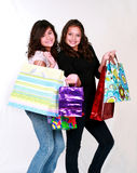 Preteens with gift bags. Pretty brunette teen girls holding gift bags Royalty Free Stock Images