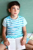Preteens handsome boy with book tired closed hes eyes. Preteens handsome boy with book  tired closed hes eyes Royalty Free Stock Image