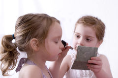Pretend play. Sisters doing makeovers Stock Photo