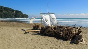 Quirky beach art: a sailing ship made out of driftwood. A pretend `ship` made out of branches, bamboo and other flotsam that`s washed ashore, bound together with Royalty Free Stock Image
