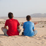 Pretending to meditate. Two boys pretending to meditate in dunes of Corralejo Royalty Free Stock Photography