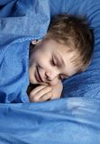 Pretending to sleep. Boy, pretending to sleep, in blue bedclothes stock photography