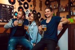 Pretmensen die bij bar weg het drinken en lach kijken royalty-vrije stock fotografie