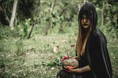 Preto asiático do vestido da mulher como o Ceifador da morte e de guardar a abóbora fotos de stock