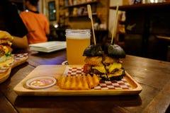 Preto do carvão vegetal do hamburguer do presunto na placa e na cerveja de madeira Imagens de Stock Royalty Free