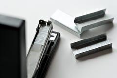 Preto do grampeador com os clipes de papel isolados no fundo branco fotografia de stock royalty free