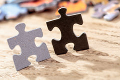 Preto e Grey Jigsaw Puzzle Pieces na tabela Fotos de Stock Royalty Free