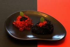 Preto e vermelho Caviar vermelho e preto apetitoso delicioso com as folhas de hortelã na placa preta da argila no fundo de contra imagem de stock