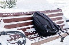 Preto esquecido, trouxa dos esportes em um banco velho no parque no inverno imagens de stock