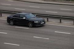 Preto luxuoso Audi A8 do carro que apressa-se na estrada vazia Fotos de Stock