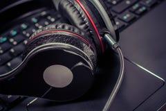 Preto pequeno auriculares prendidos do jogo que encontram-se no teclado de um caderno Fotografia de Stock Royalty Free