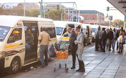 Minibus taxi rank in South Africa. Pretoria, South Africa, June 7 - 2018: Commuters at minibus taxi rank looking at oranges on sale stock photography