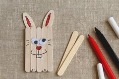 Pretpaashaas van houten stokken en viltpennen op ruw canvas wordt gemaakt dat royalty-vrije stock foto