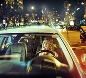 Prett  lady riding across the city in the dead of the night Royalty Free Stock Photos