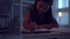 Prettig meisje die haar huiswerk in de avond thuis doen stock videobeelden