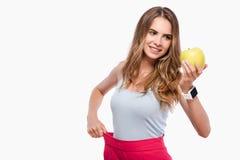 Prettige blije slanke vrouw die een appel houden Royalty-vrije Stock Afbeelding