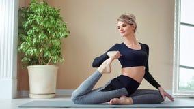 Prettige glimlachende Europese geschiktheids jonge vrouw die het uitrekken op mat maken zich bij moderne yogastudio stock video
