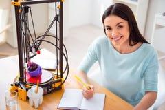 Prettige glimlachende vrouw die 3d printer met behulp van Stock Foto's