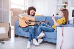 Prettige jonge de kamergenoot van de meisjesopname het spelen gitaar royalty-vrije stock afbeelding