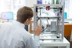 Prettige jonge ingenieur die op 3D printer in actie letten royalty-vrije stock foto's