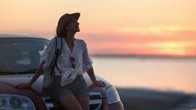 Prettige jonge reisvrouw ontspannende het golven haarzitting op autobonnet die van het zeegezicht van de schemerzonsondergang gen stock footage