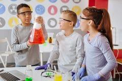 Prettige jongen die chemisch experiment aantonen aan klasgenoten stock fotografie