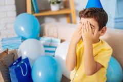 Prettige jongen die op verjaardagsverrassing wachten terwijl het behandelen van zijn ogen Royalty-vrije Stock Foto's