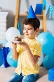 Prettige jongen die in partijhoed zijn verjaardagscake bekijken Royalty-vrije Stock Afbeelding