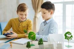 Prettige jongens die hun vaderswerkplaats met duidelijke belangstelling onderzoeken Royalty-vrije Stock Foto