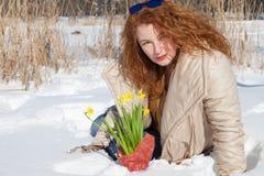 Prettige modieuze krullende haired vrouwenzitting in sneeuw met gele narcissen stock afbeelding