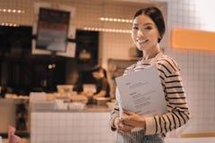 Prettige mooie jonge vrouw die als serveerster in comfortabele cafetaria werken stock afbeeldingen