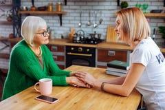 Prettige oma die haar zorg met jong-volwassene delen die dame begrijpen stock fotografie