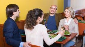Prettige vrolijke middenstandmensen die van voedsel en wijn genieten Stock Foto