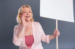 Prettige vrouw het schreeuwen slogans op middelbare leeftijd en het houden van banner stock foto