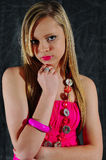 Pretty. Young female fashion model with her hand under her chin looking directly at the camera wearing a stylish pink dress and jewelery Stock Image