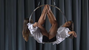 Pretty acrobats performs a trick in the aerial hoop stock video footage