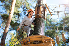 Pretty active woman hiding behind a tree. Outdoor games. Cheerful energetic slender woman sitting behind the tree and looking at the rope road while doing Royalty Free Stock Image