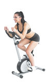 Pretty active woman training on an exercise bike Royalty Free Stock Photography
