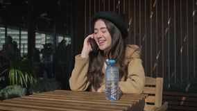 Pretty adolescent girl is answering on mobile call in open terrace of cafeteria. Charming teen girl is calling by mobile phone in cafe on street. She is smiling stock footage