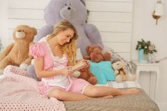 Pretty adult girl with her secret diary in her white bedroom with many plush teddy bears royalty free stock image