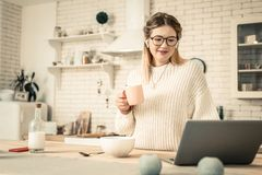 Pretty adult lady drinking morning coffee and checking information royalty free stock images