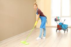 Pretty adult woman moping floor. In corridor Stock Image