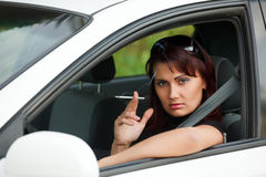 Pretty adult woman sitting in a car Stock Images
